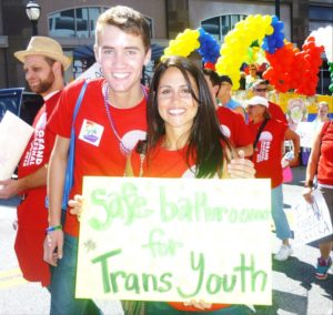"""Austin and Maru holding a sign that read, """"Safe bathrooms for trans youth"""""""