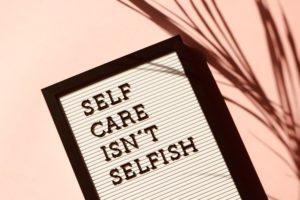 Board with Self Care Isn't Selfish written on it.