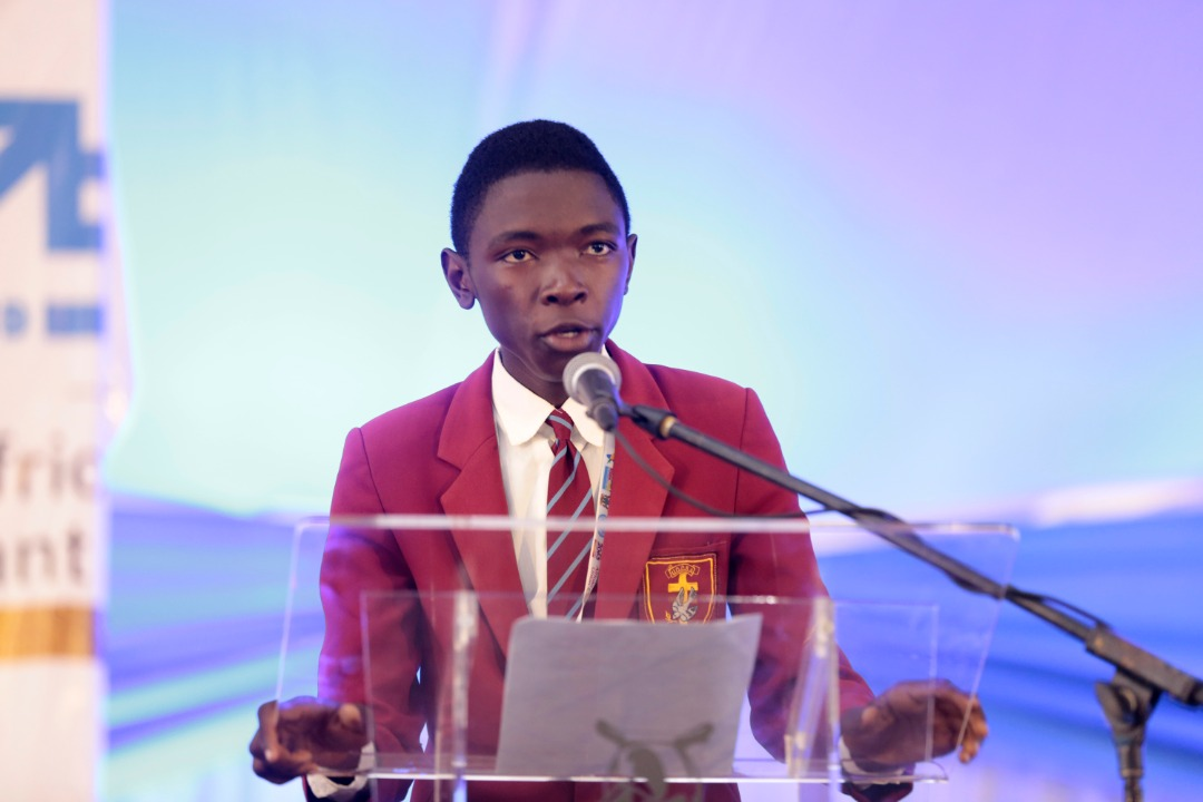 Nkosilathi is pictured giving a speech, holding a podium and speaking into a standing microphone.