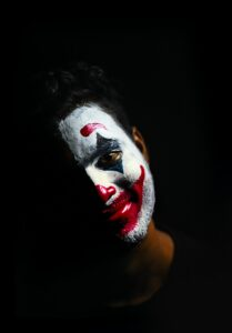 A figure wearing clown makeup is pictured against a black background.
