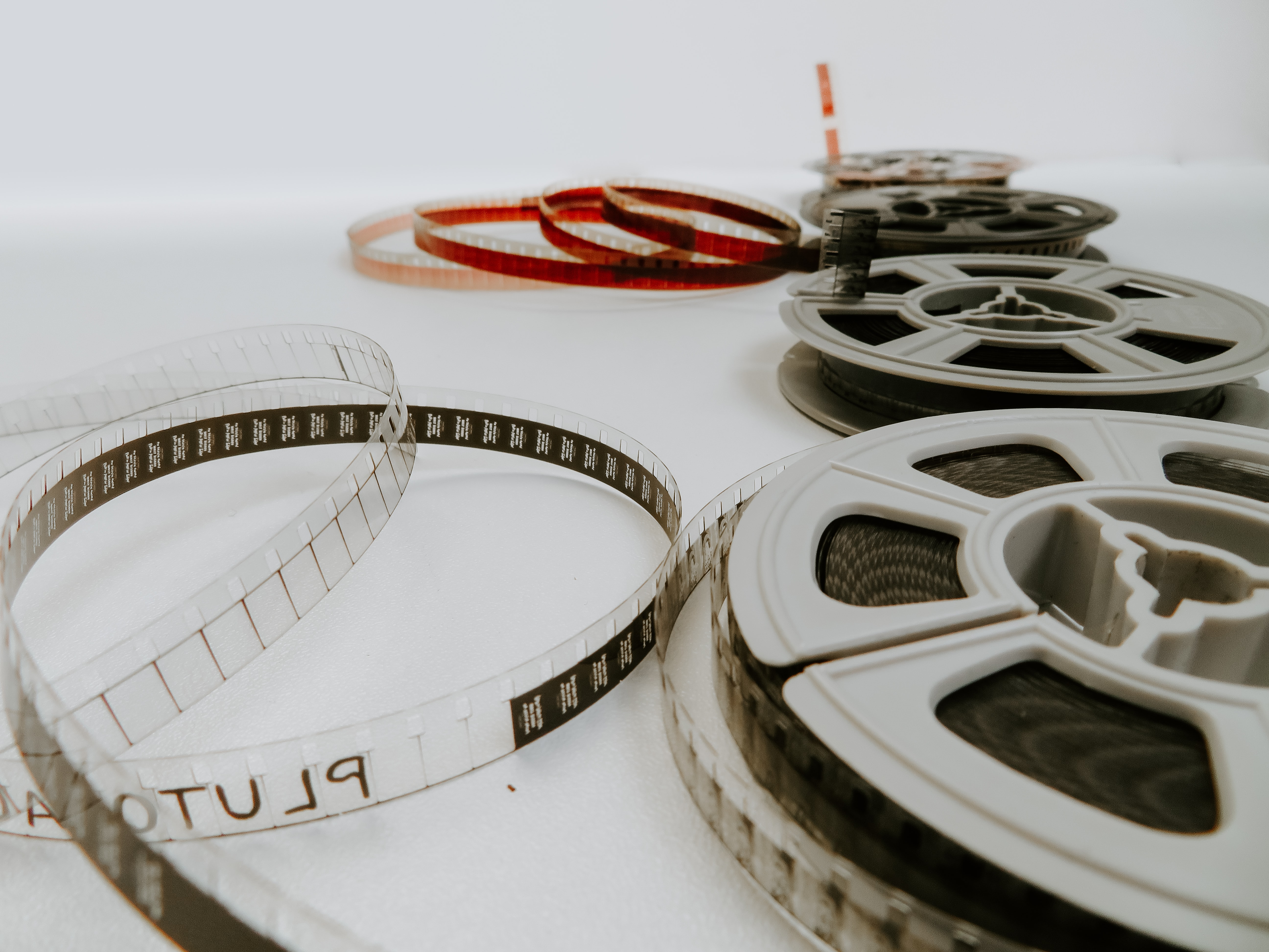 Roles of cinama film laying on the ground with a white background.